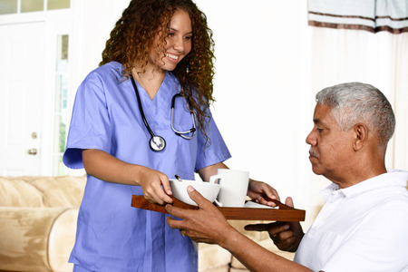 senior female: Health care worker helping an elderly man Stock Photo