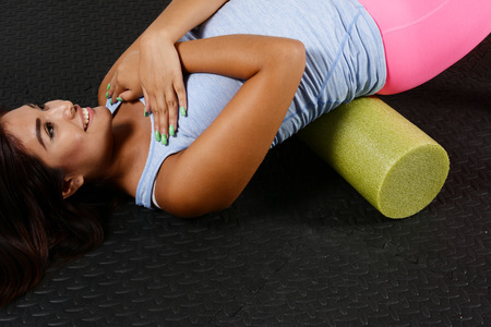 the roller: Woman using a foam roller after a workout