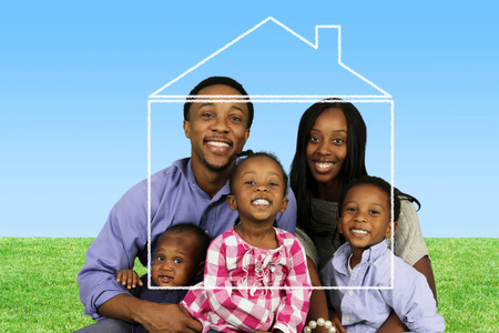 home purchase: Young family together outside of their home