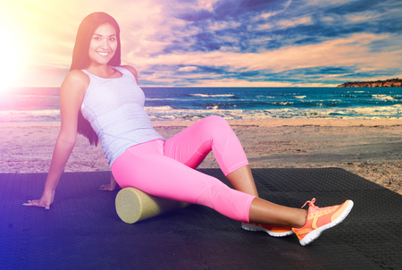 roller: Woman using a foam roller after a workout