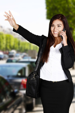 catching taxi: Business woman catching a ride in taxi Stock Photo