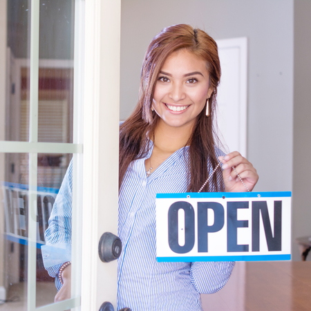 Woman opening her store with an open sign Imagens
