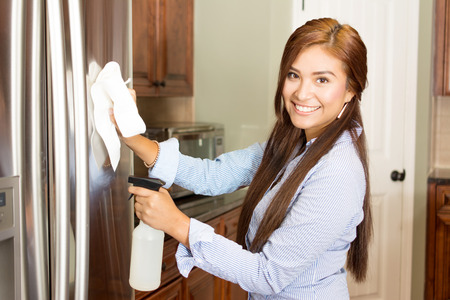fridge: Woman cleaning her kitchen with a spray bottle