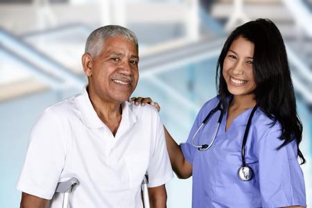 terapia grupal: Enfermera dando terapia física para un paciente anciano Foto de archivo