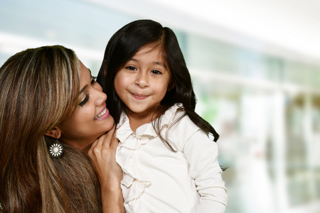 hispanic woman: Happy young woman who is standing with her daughter