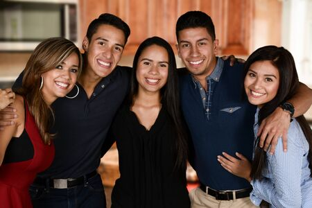hispanic family: Group of friends together in their home