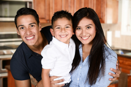 hispanics: Happy young couple who are standing with their son