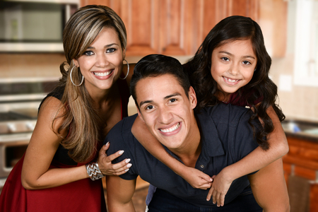hispanic kids: Happy young couple who are standing with their daughter