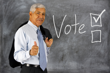 Old man with Voting boxes displayed on a chalk board Фото со стока