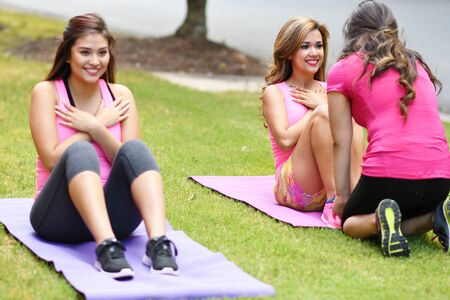 outdoor fitness: Group of women doing a group fitness workout together Stock Photo