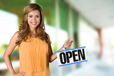 Woman opening her store with an open sign Foto de archivo