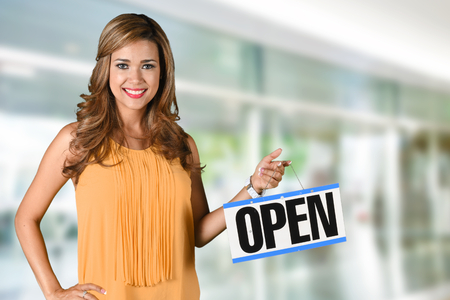 store sign: Woman opening her store with an open sign Stock Photo