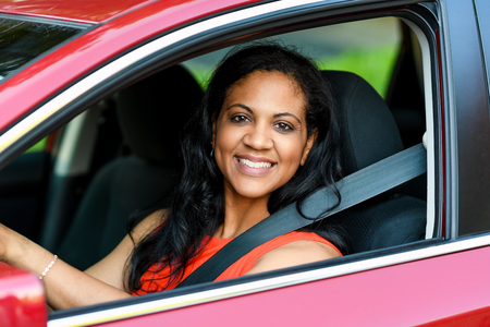 Woman holding up keys to her new car photo