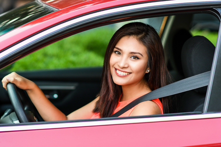 Woman holding up keys to her new car Foto de archivo