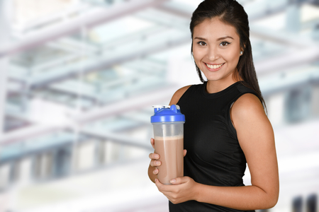 shake: Woman enjoying a protein shake after her workout