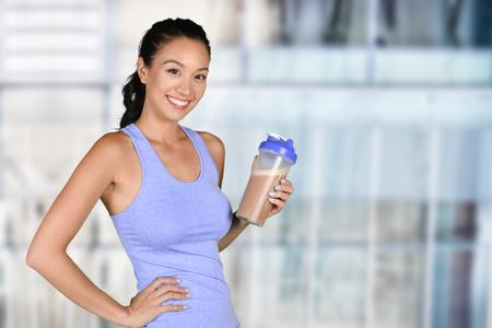 여자는 그녀의 운동 후 단백질 쉐이크를 즐기고