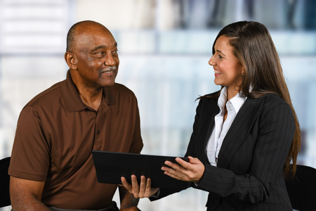 Confident businesswoman who is working with an elderly client Stock Photo