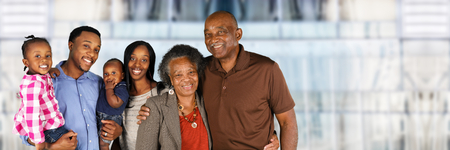 black guy: Elderly African American Man and woman posing together with their family