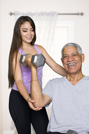 Elderly man working out with a personal trainer Stock Photo
