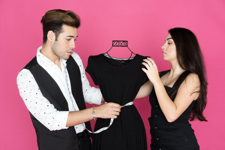 Fashion designer and his assistant working at their studio