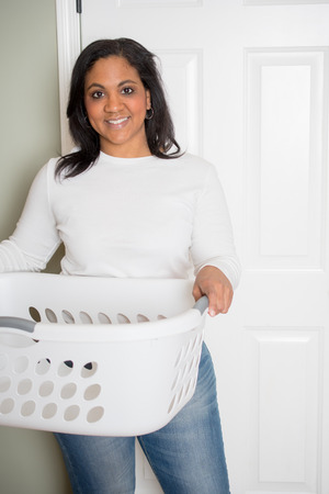 Woman happily doing laundry at her home Stock Photo