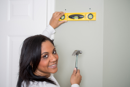 Woman with a hammer repairing her house Stock Photo