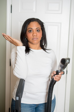 Woman using the vaccum on her house