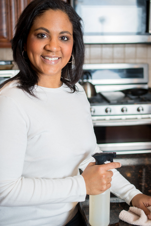 Hispanic woman cleaning her kitchen counter with a cloth Stock Photo
