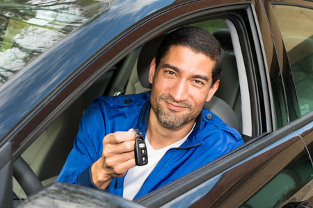 Man holding up the keys to his new car