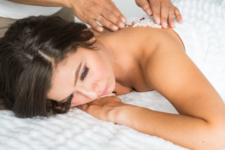 Hispanic woman at the spa gettting a massage Stock Photo