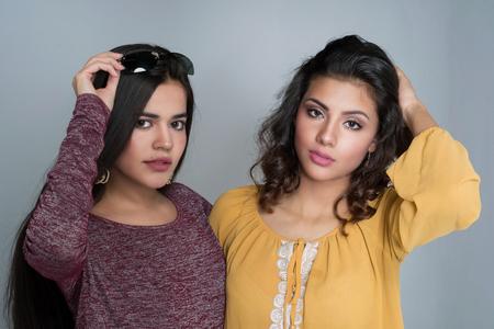 Two hispanic teenage sisters posing in a group