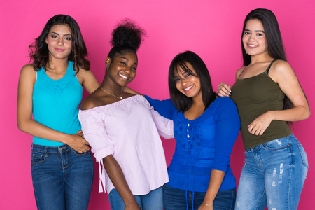 Group of very diverse teen friends on pink background