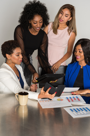 Group of four minority businesswomen working together in the office