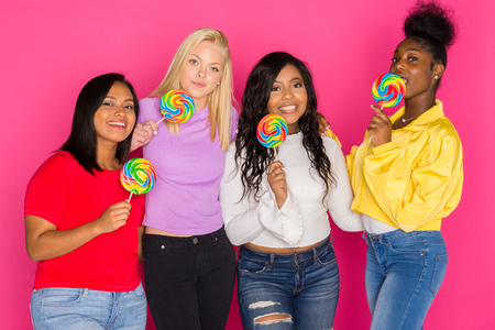 Group of female diverse teenage friends on pink background
