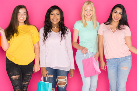 Group of four teen girls having fun together on a pink background