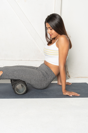 Teenage girl working out in her gym with a foam roller
