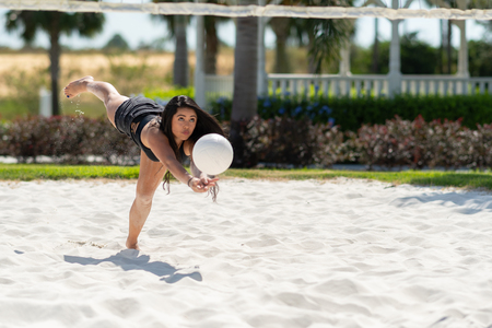 Teenage girl playing volleyball on a sand court