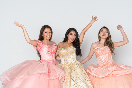 Group of three teenage hispanic girls wearing quinceanera dresses