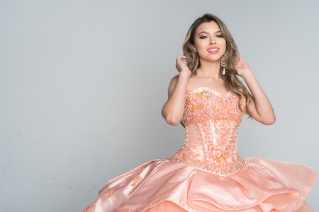 Hispanic teen girl wearing a quinceanera dress for her party Stock Photo