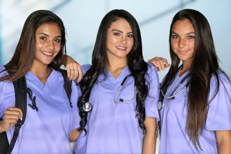 Three happy hispanic nursing students at school