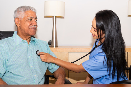 Home health care nurse assisting an elderly patient in his house