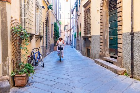 Woman going for a bike ride in scenic Italy 免版税图像 - 128528249