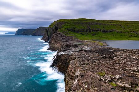 Waterfall from a lake going into the Ocean in the Faroe Islands Banco de Imagens