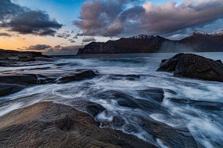 Waves crashing on rocks at sunset in Senja, Norway during the summer