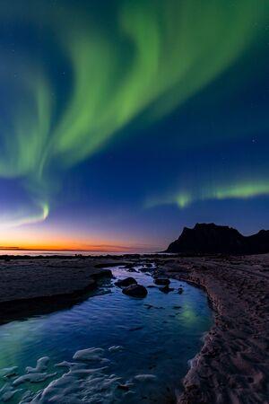 Northern lights shining in the Lofoten Islands at Uttakleiv Beach Imagens