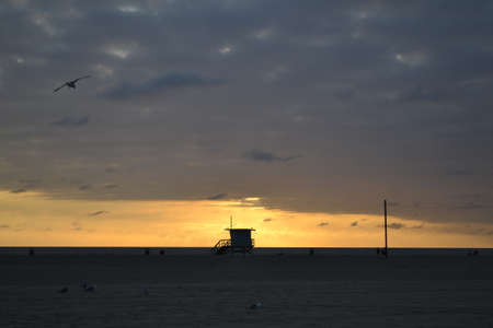 Sunset by Venice Beach with a lifeguard cabin in front of the sun photo