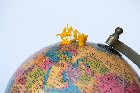 Plastic soldiers on top of a globe Stock Photo