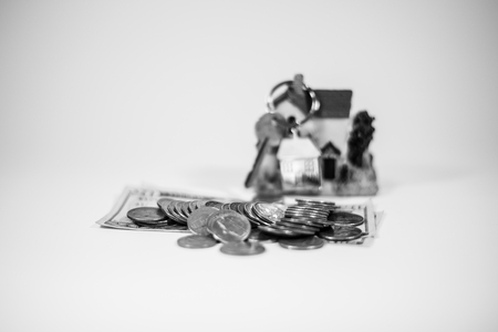 Pile of US dollars (coins and bills) and a set of house keys with a miniature house on top