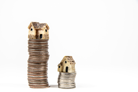 Miniature houses on top of piles of coins to represent differences in prizes