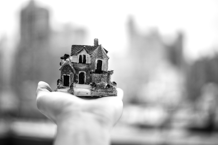 Miniature house on a hand with NYC skyline in the background